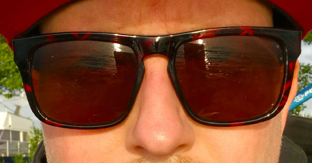 Close up selfie of sunglasses reflecting a lake during sunset.